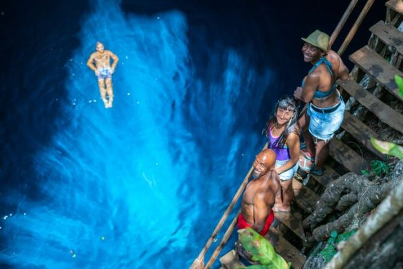 A man floating in a blue cenote in Mexico