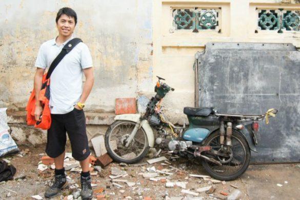 MAn standing in front of a motorbike in Vietnam