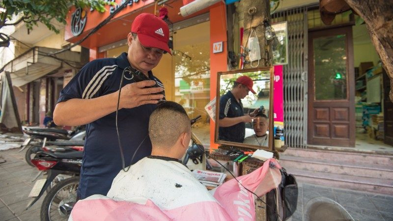 A barber provides haircuts on the street