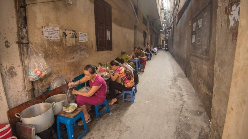 A line of diners eat soup in a Hanoi laneway