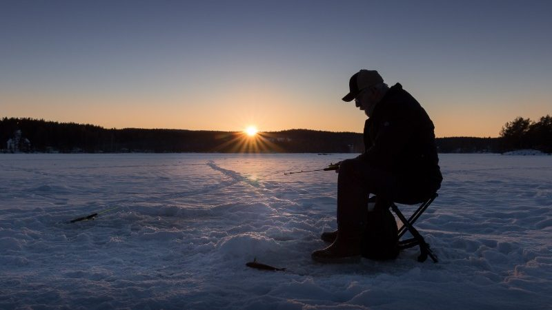 A fisherman sits on the ice waiting to catch a fish in Norway