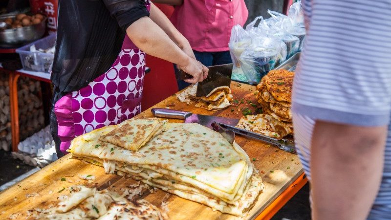 A woman cuts up spring onion pancakes in the market