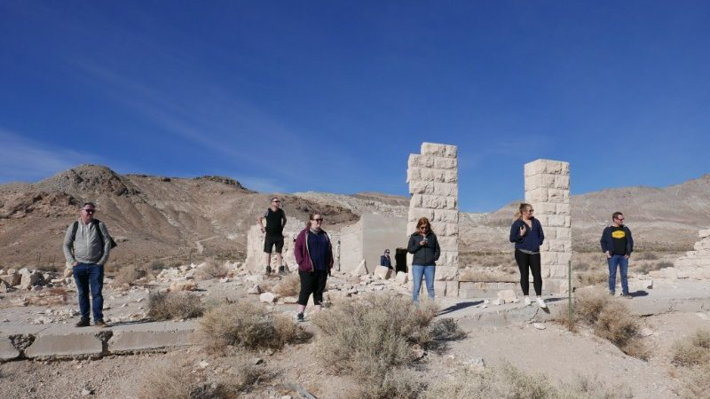 Passengers stand around in a deserted Death Valley town