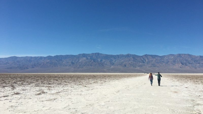 Two travellers walk across Badwater Basin in Death Valley