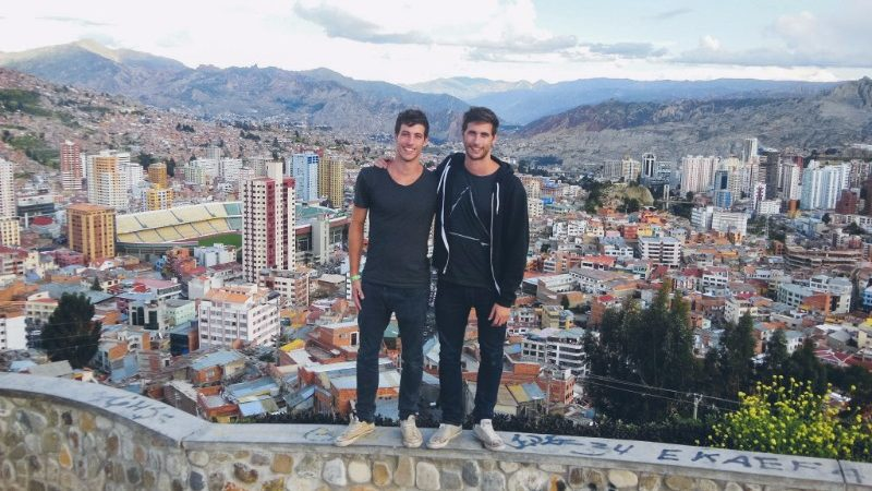 Two brothers stand on a wall overlooking the city