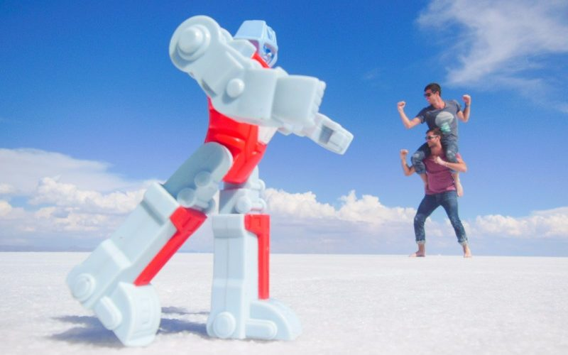Two men fight a giant Transformer figure on the salt flats