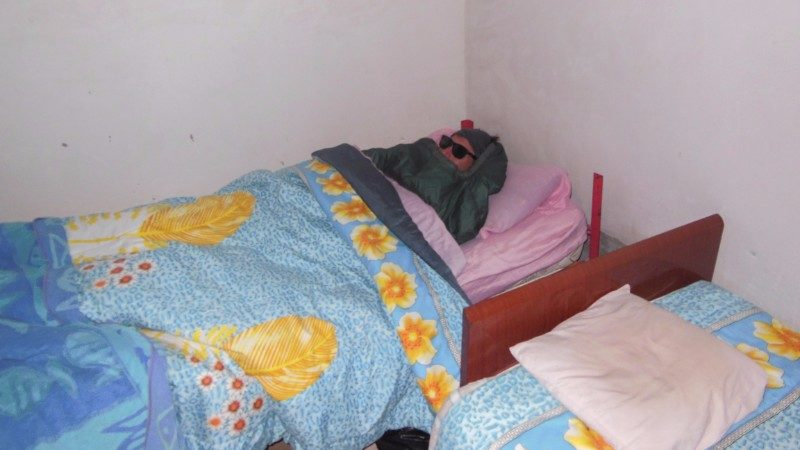 A man wearing sunglasses is rugged up in bed
