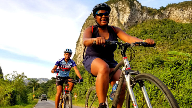 Two cyclists ride through Vinales