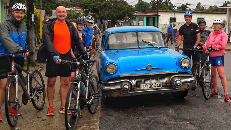 A group of cyclists pose in front of a vintage car in Cuba
