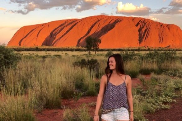 Izzy stands in front of Uluru at sunset