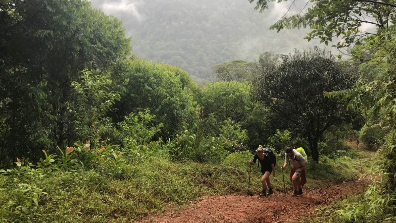 Two trekkers on a muddy path in Costa Rica