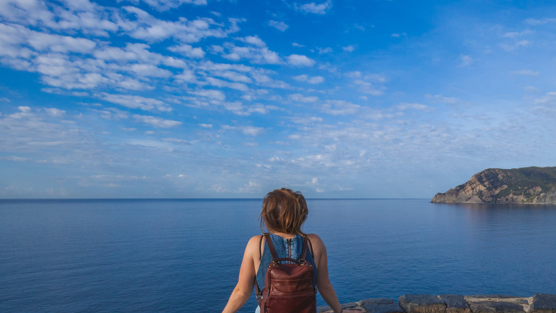 A woman looks out to sea in Italy
