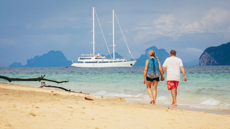 A couple walking down the beach in Thailand with an Adventure Cruise ship in the sea in front of them.