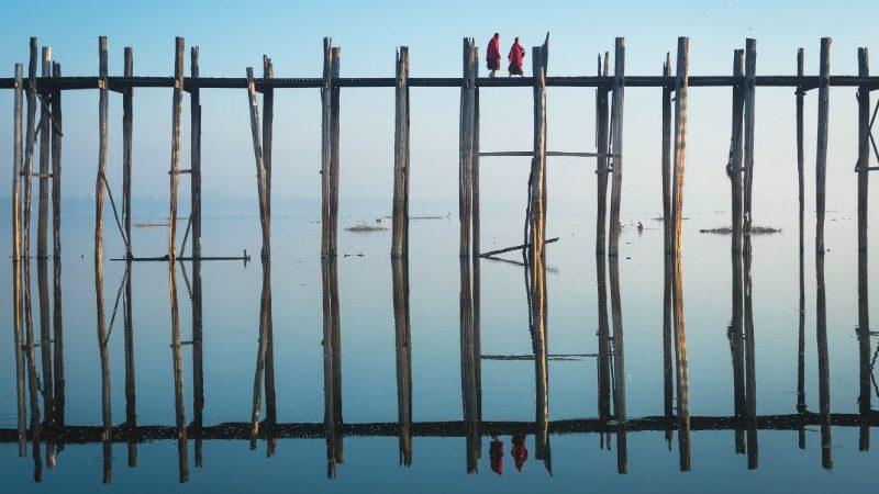 Two monks walk across U Bein Bridge in Myanmar at dawn