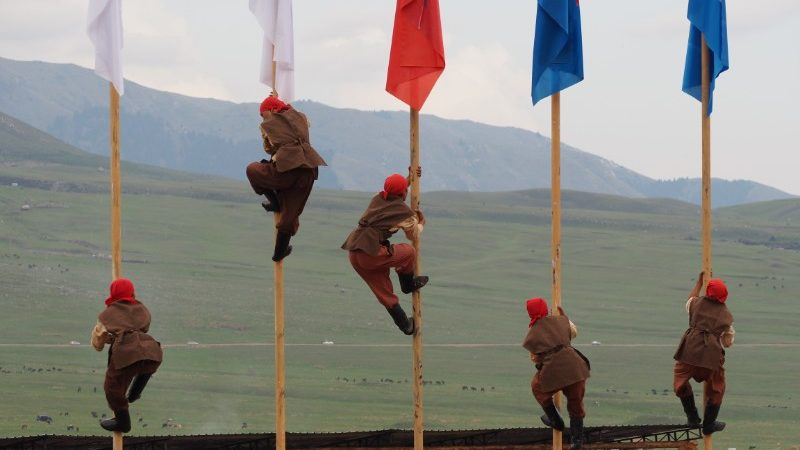Five competitors climb flagpoles at the World Nomad Games