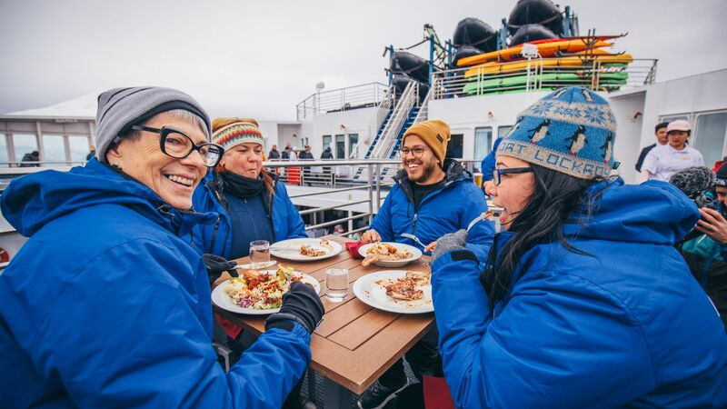 A group of travellers in blue jackets eating on the deck of a ship in Antarctica