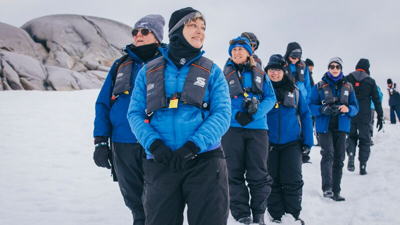 A group of travellers rugged up against the cold in Antarctica