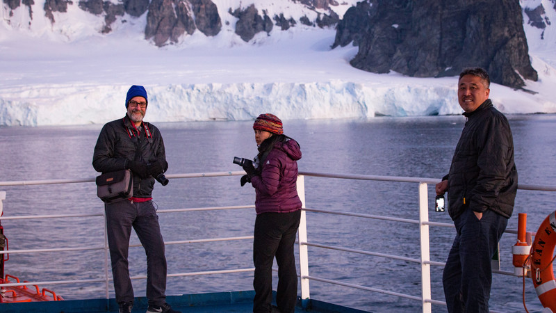 Three travellers on deck in Antarctica