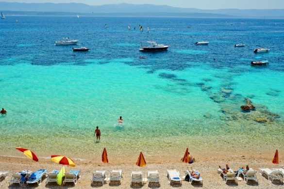Boats and swimmers on beach in Brac, Croatia