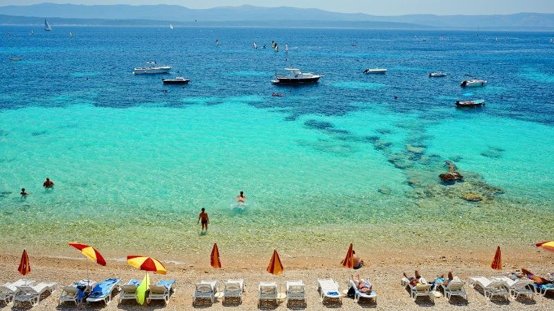 Boats and swimmers on beach in Brac, Croatia