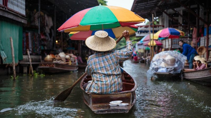 Woman rowing through floating market