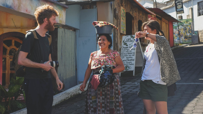 Two travellers meet a local woman in Guatemala