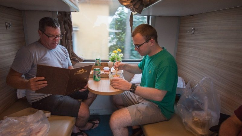 Two travellers have dinner on the train