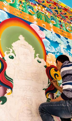 A man painting a Tibetan Buddhist Gompa