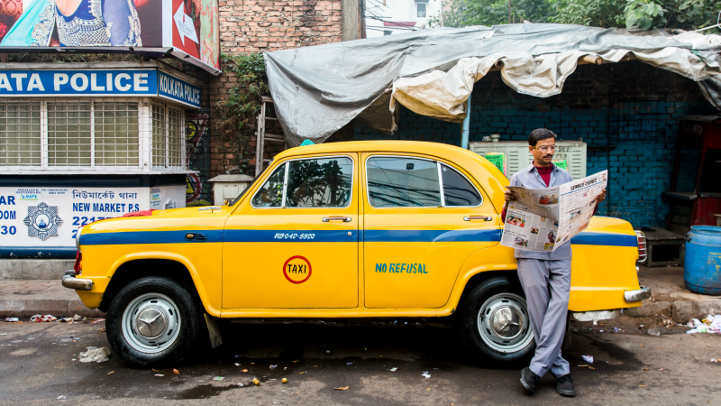 Taxi driver reads newspaper in Kolkata, India