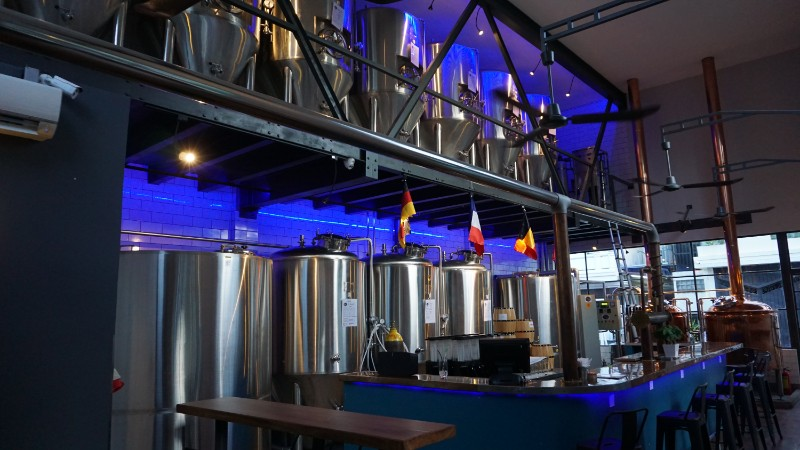 Beer kettles behind bar at Hops Brewery