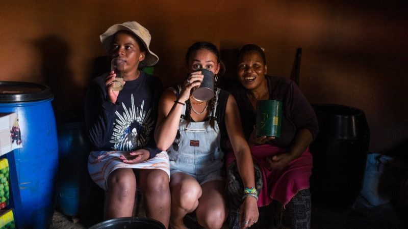 Three women drinking in a shebeen