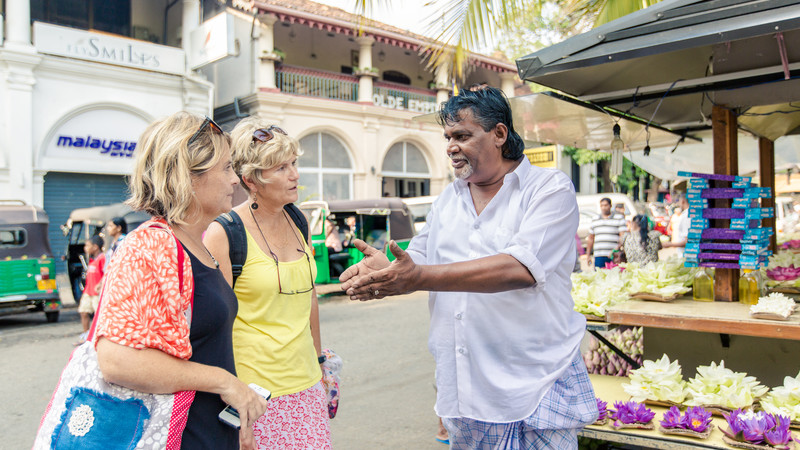 Travellers chat with a local in Kandy, Sri Lanka