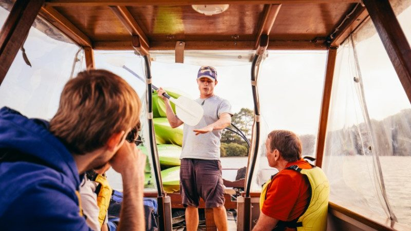 Tour guide and travellers on boat in Bay of Islands
