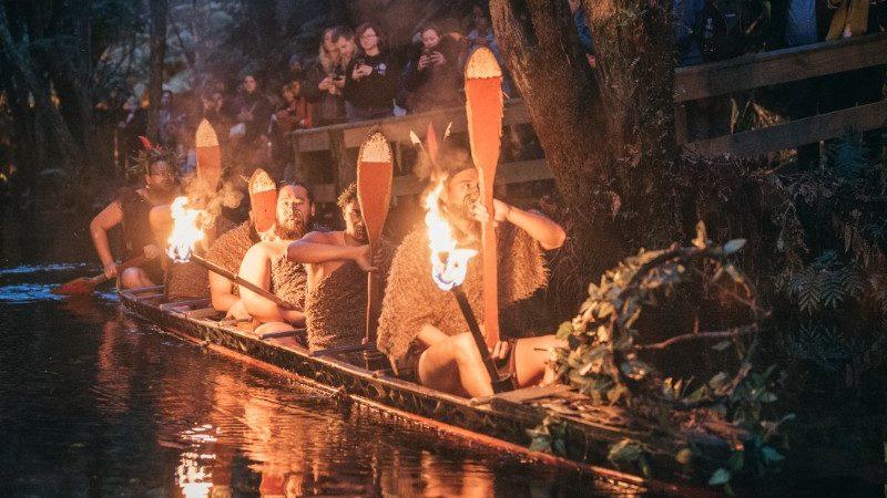 Maori warriors paddling in canoe