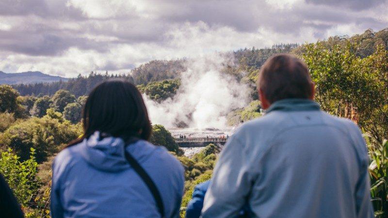 Travellers watching Pohutu geyser erupt