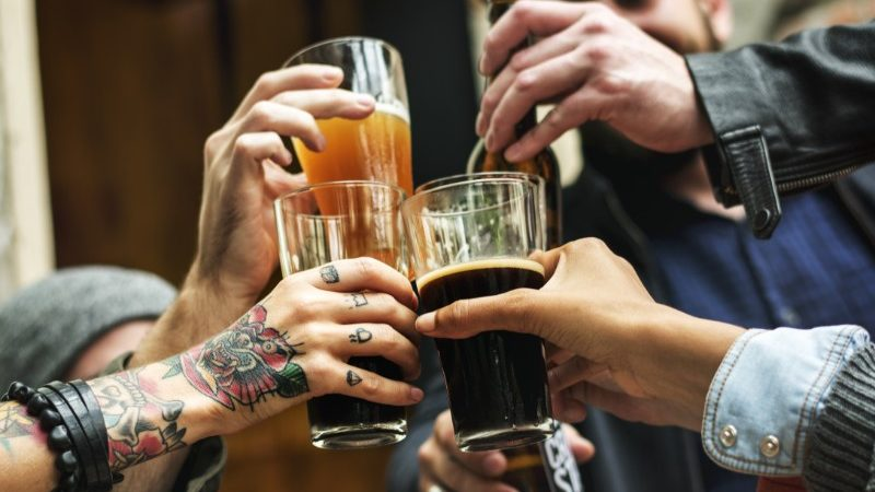 Drinkers clinking beer glasses together