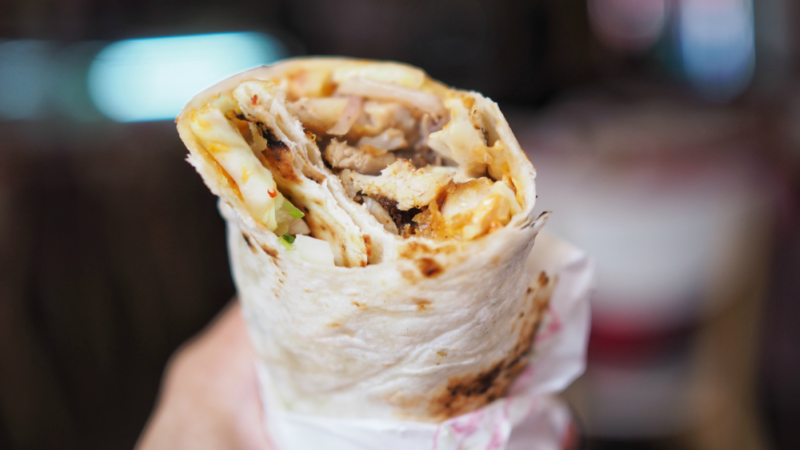 Hand holding a chicken shawarma wrap