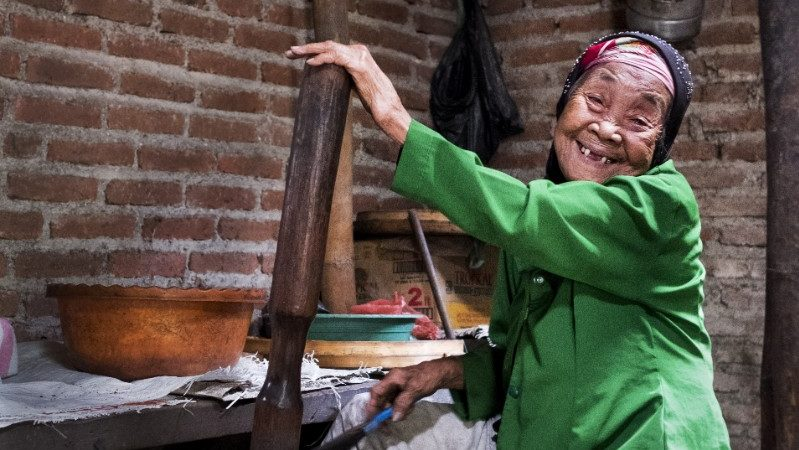 An old woman grinding coffee beans