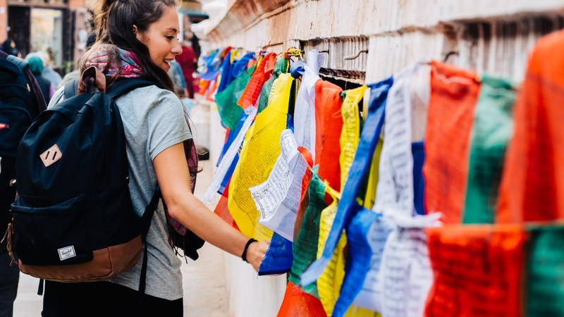 A young woman walks past a row of prayer flags