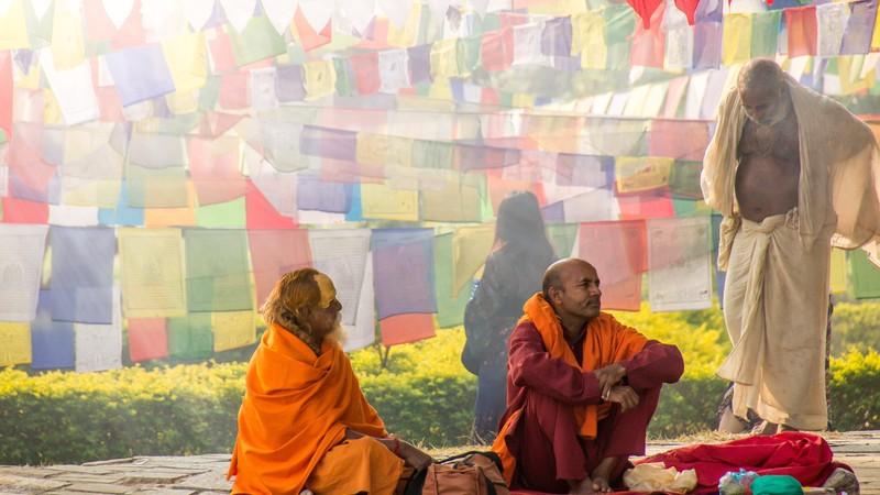 Three sadhus sit under colourful prayer flags