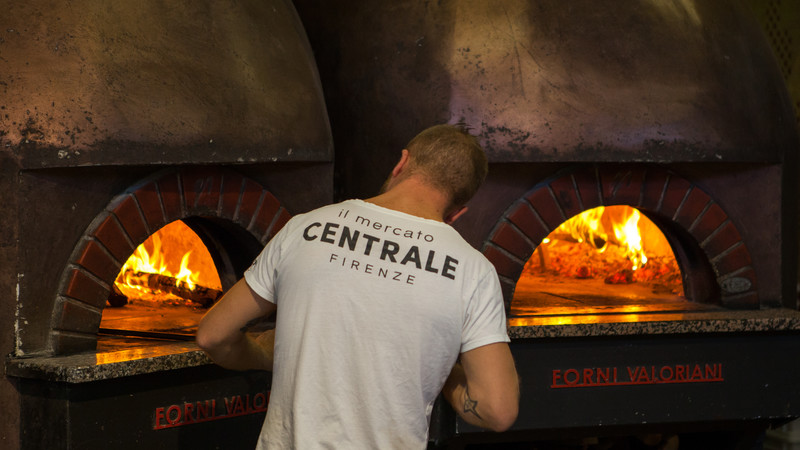 Man in front of a hot pizza oven