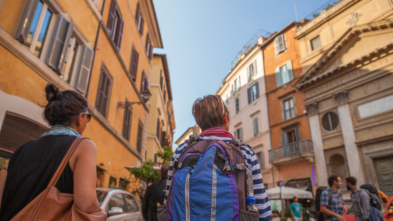 Backpackers walk through Rome in Italy
