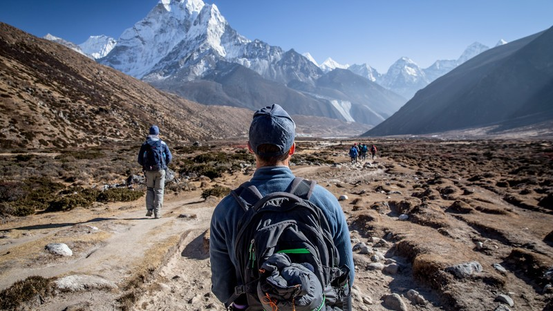 Man in backpack looks at Mt Everest