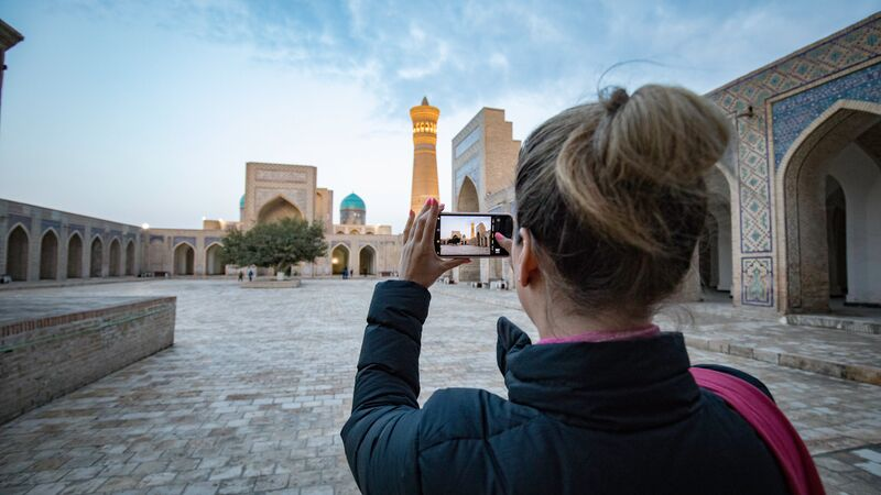 A woman taking a photo of a building in Uzbekistan