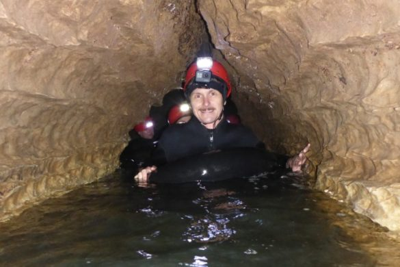 Travellers in water in Waitomo cave