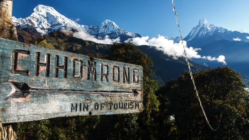A trail marking and the Annapurna Mountain Range on the Base Camp Trek
