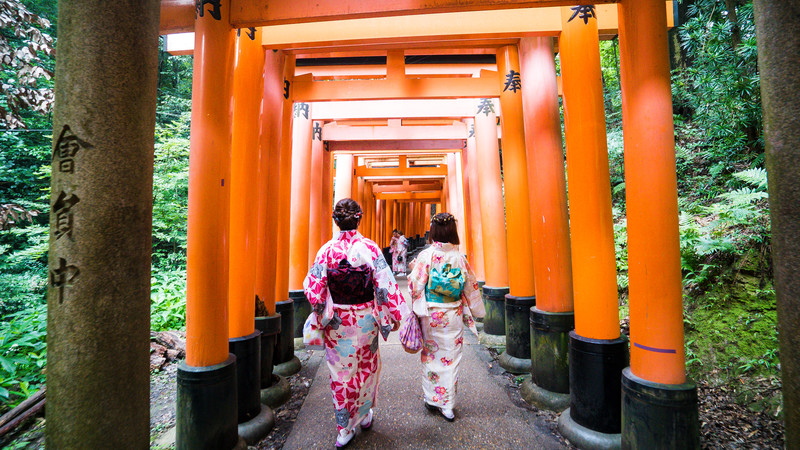 Two geishas walk through the Fushimi Shrine
