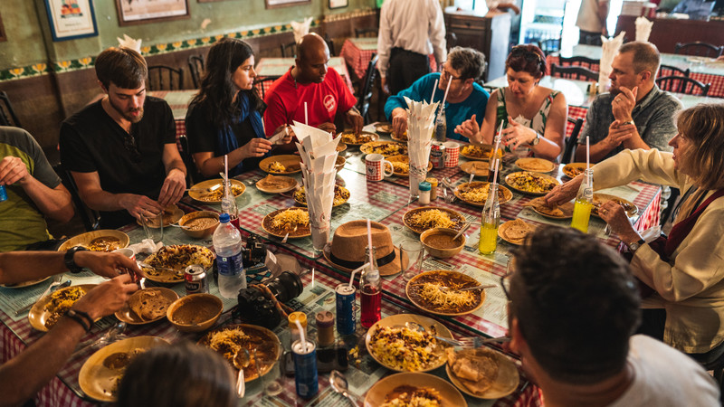 Tour group sharing meal in India. Image by Benemac.