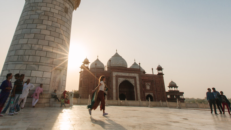 A woman walks around the Taj Mahal