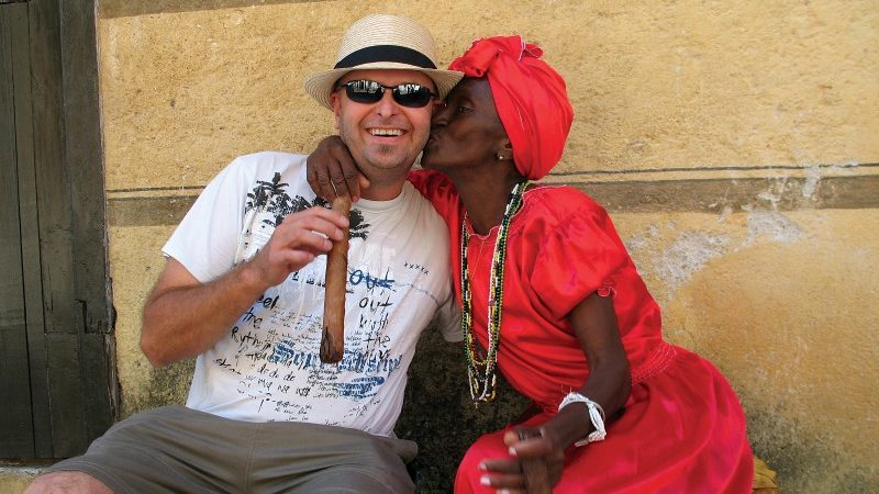 Traveller with a cigar and local woman in Havana.